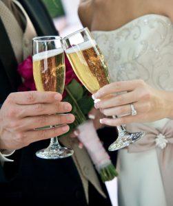 un couple de mariés trinque avec des flutes de champagne